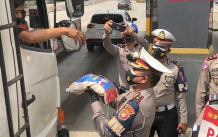 Ilustrasi polisi bagikan beras di gerbang tol. (INDOZONE/Samsudhuha Wildansyah)